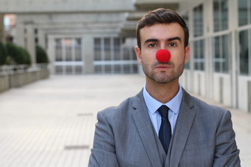 Businessman with a red clown nose isolated