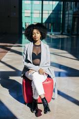 Stylish ethnic model sitting on lounge