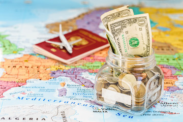Holidays money savings in a glass jar with passport and aircraft toy on world map, copy space, mock up, holiday concept