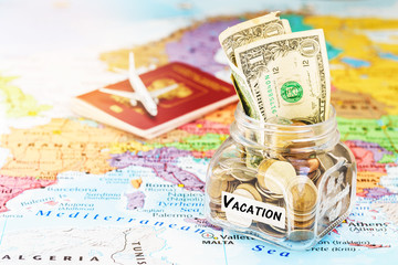 Vacation money savings in a glass jar with passport and aircraft toy on world map, selective focus