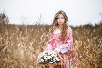 Beautiful little girl with curls of hair in a red woven scarf is standing in the field.  In the hands of the child a wicker basket with wild flowers.