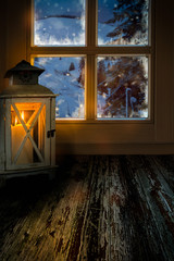 Warm light in a cold winter night, lantern in front of a frozen window