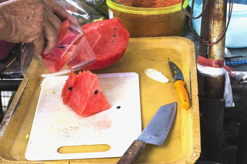 Men's hands are sliced watermelon.
