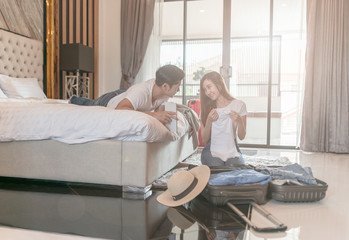 Happy couple packing suitcase on floor in room use tablet for search travel trip online