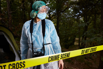 Forensics researcher photographing a blood  at a murder scene