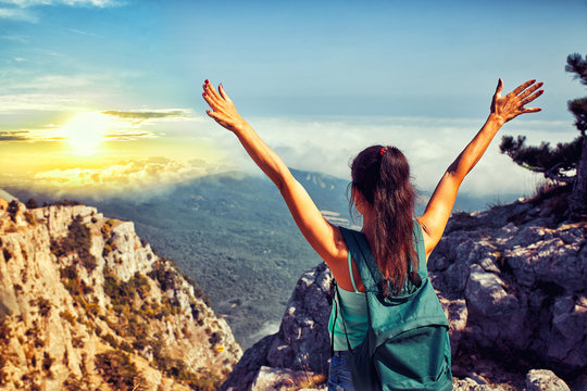 Happy Woman raised hands at sunset mountains