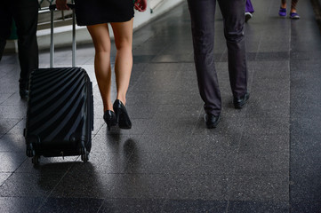 traveller man and woman walk and talk together with black luggage, business travel