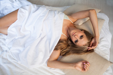 girl in lingerie is sleeping in bed in the morning, white