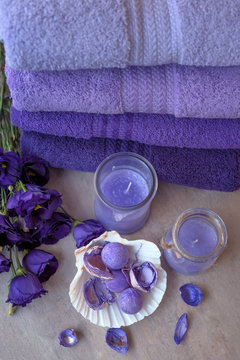 Purple towels, flowers and candles. Lavender aromatherapy. Spa treatments and relaxation.