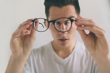 Closeup portrait of young man with glasses. He has eyesight problems and is squinting his eyes a little bit. Handsome guy is holding his eyeglasses right in front of camera with one hand. The concept