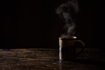 Hot drink against dark background on wooden surface.