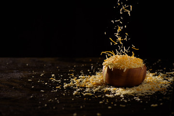 Cheese falling into small wooden bowl against a dark background.