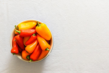 Colorful peppers in blue bowl on white background.