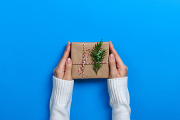 Female hands holding gift box on Blue background