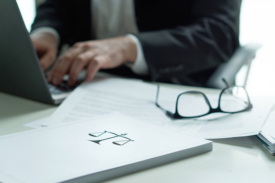 Lawyer working in office. Attorney writing a legal document with laptop computer. Glasses on table. Pile of paper with scale and justice symbol. Law firm and business concept.