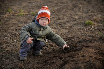 A young boy tries to help his parents plant potatoes in a vegetable garden in the village