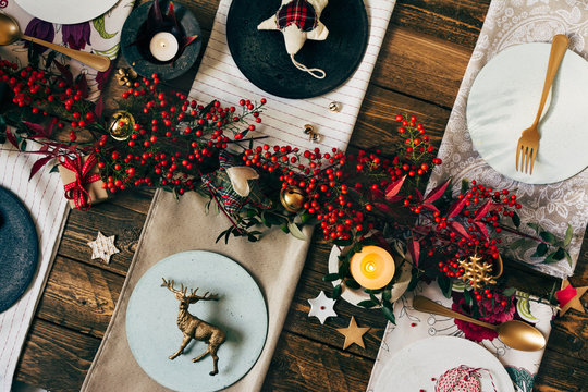 Holiday Gold place setting, funny Christmas table with ornaments and natural berries, on wooden table