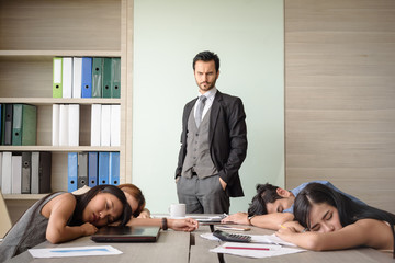 caucasian angry boss looking at employees sleeping in office