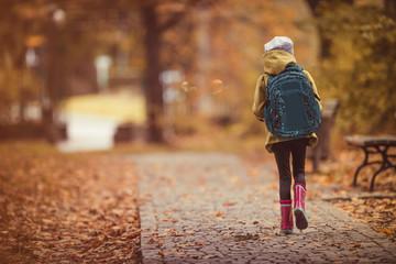 Travel to school. Girl walking through park. Autumn theme.