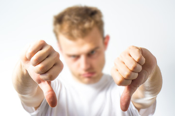 man with a finger down on a white background, thumb down gesture , bad signal, no okay