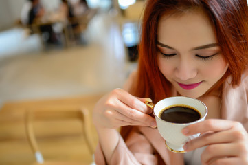 Portrait of beautiful face woman and hand holding a cup of coffee in her hand in blur background coffee shop, she drink coffee in the morning