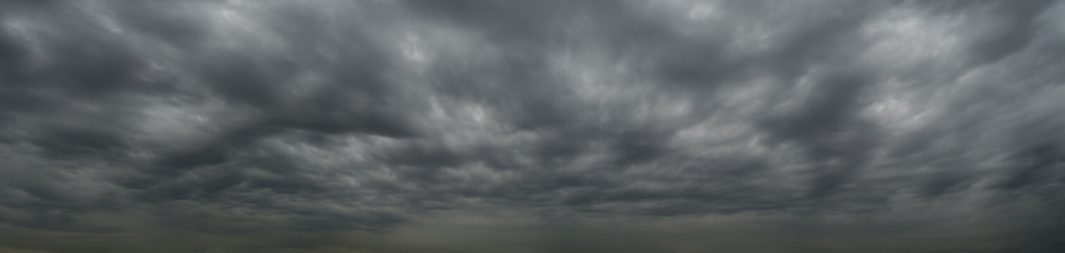 Dark clouds before a thunderstorm, tornado, hurricane, in the vast sky. Dramatic sky background