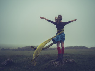 Woman with scarf in the wind raising her arms