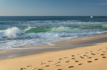close up on breaking wave coming to shore on sandy beach of atlantic coast, capbreton, france