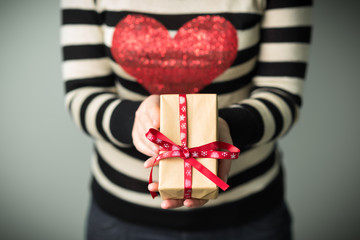 Christmas background. A girl in a striped sweater with a red heart on her chest. Girl with a Christmas gift in hands. Gifts for men. Merry Christmas. Knitted mittens. Box with gifts.