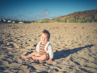 Cute little baby sitting on the beach