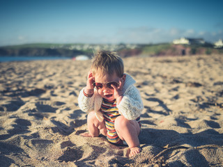 Baby with sunglasses on the beach
