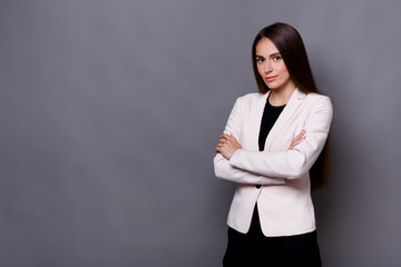 Beautiful young caucasian businesswoman studio shot on grey background