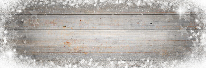 Christmas background with snow, stars and sparkling light on wooden board
