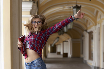 portrait of a young beautiful long-haired girl with glasses in shirt and jeans. Emotionally jumping with a book in hand