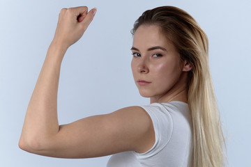 attractive confident young woman shows biceps. Portrait on a white background, expressive look at the camera
