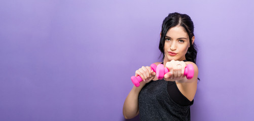 Happy young woman working out with dumbbell Wall mural
