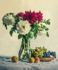 A bouquet of chrysanthemums in a vase and a dish with grapes and peaches