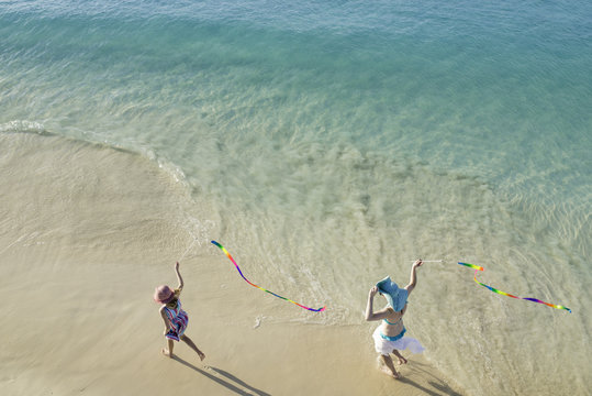 Aerial View of Mother and Girl Running Along Tropical Beach on Vacation with Streamers