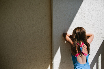 little girl facing a wall