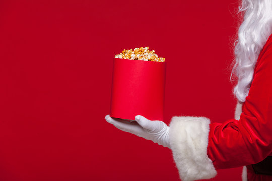 Christmas. Photo of Santa Claus gloved hand With a red bucket with popcorn, on a red background