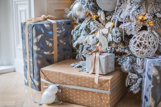 Новогодние подарки лежат под елкой. Заснеженная елка в белых и серебряных тонах