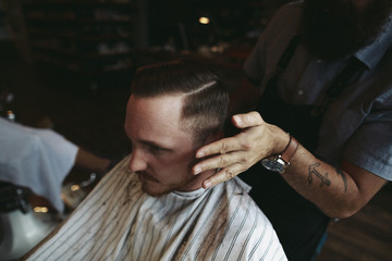 Stylish modern barber giving man a classic haircut - finishing touches