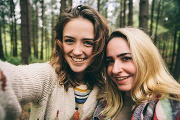 Two teenage girls taking a selfie in woodland