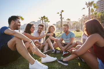 Group of friends sitting outside in circle talking Wall mural