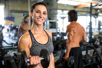 Fun playful energetic female health and nutrition fitness expert exercising with weights at gym