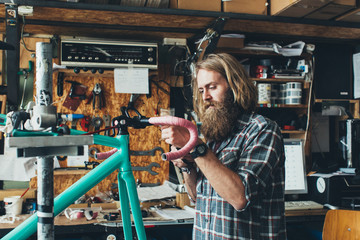 Young Bicycle Mechanic Assembling Fixed Gear Bike in Workshop