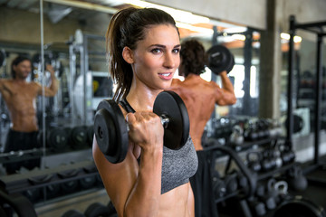 Pretty Caucasian Woman in coed gym lifts dumbbell to lose weight, thin and strengthen arms
