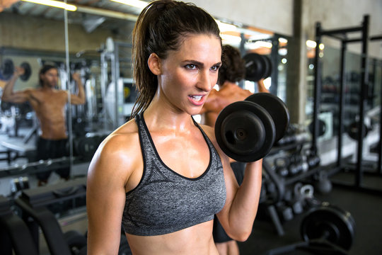 Strong fit determined confident female with fit body strengthens arms and upper body in gym