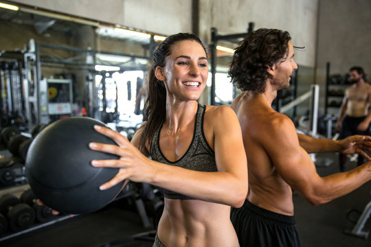 Smiling cheerful happy workout partners exercising with medicine ball at local gym as a couple