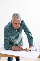 Elderly designer businessman working at office.